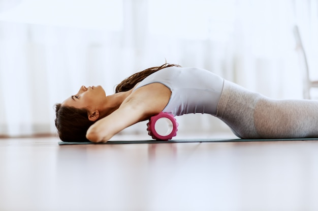 Close up of slim young woman lying on the backs and stretching it with roller.