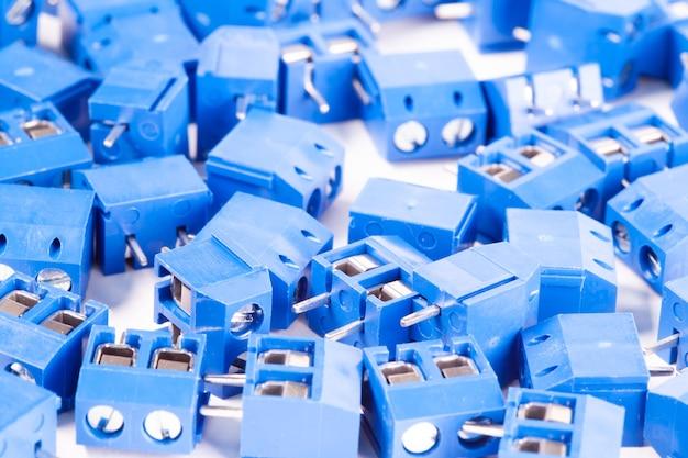 クローズアップの小さな青いコネクタパーツは白いテーブルの上にあります。強力なコンピューターと印刷機器の生産のためのコンセプト。