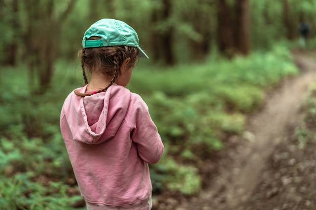 Close-up, a small child girl in a dense forest is walking along a path into the depths of the forest