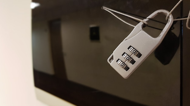Крупным планом небольшой кодовый замок закрывает электрическую панель с черной стеклянной крышкой в коридоре офисного здания.