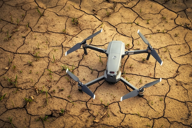 Close up small drone on brown soil in the field