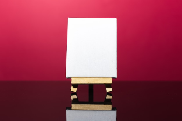 Close-up of small easel with white mockup on dark coral pink surface