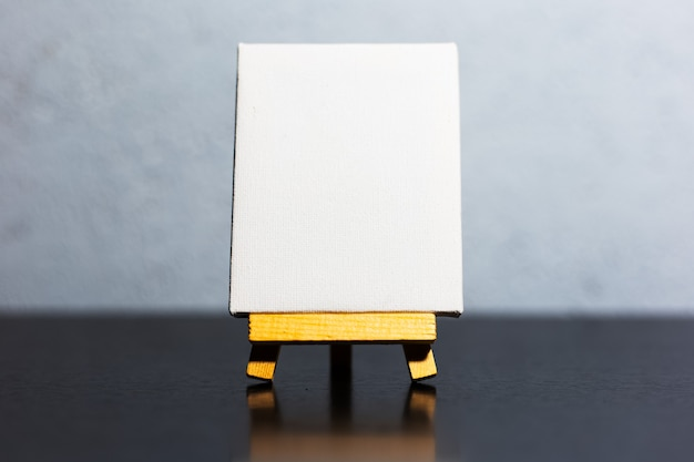 Close-up of small easel with white mockup