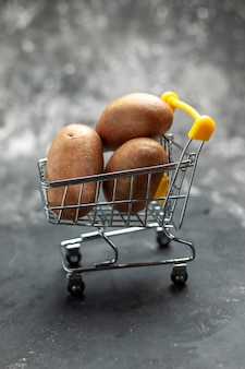 Close up on small folding shopping chart with potatoes in it