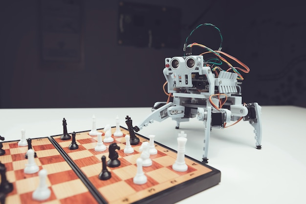 Close up. small gray robot playing chess on table.