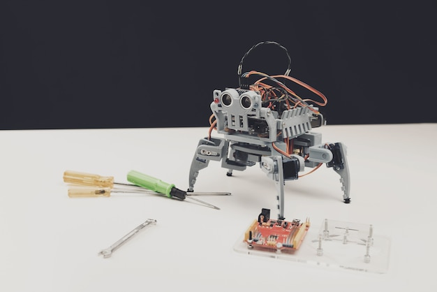 Close up. small gray robot with tools on table.