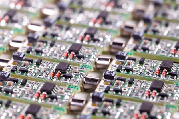 Небольшие микросхемы крупным планом лежат рядом друг с другом при производстве аудиодеталей для динамиков и компьютеров. концепция современных технологий для надежности и высокого качества