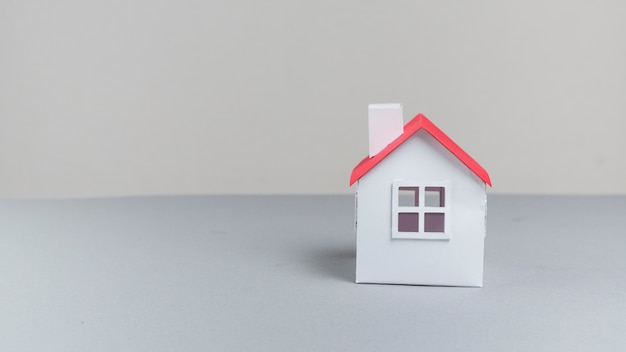 Close-up of small paper house model on grey surface
