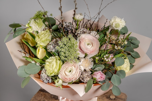 Close-up of small pink flowers bouquet in glass vase with blurred grey background. wedding or birthday, valentines day concept.