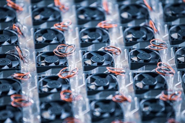 전선이있는 근접 소형 플라스틱 컴퓨터 쿨러는 컴퓨터 제조시 나무 테이블에 투명 플라스틱 패키지에 놓여 있습니다. 컴퓨터 및 장비 공장 개념