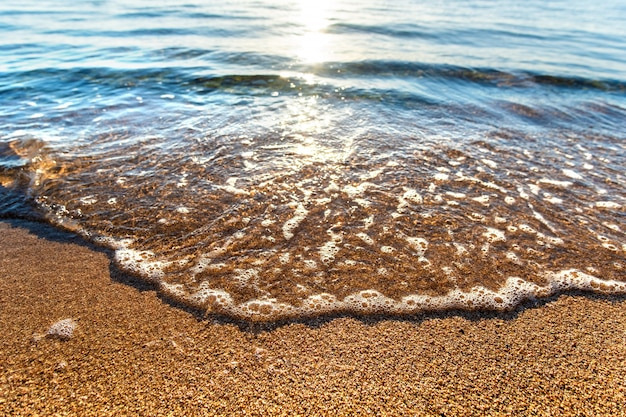 Close up of small sea waves with clear blue water over yellow sand beach at summer sunny shore.