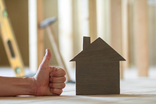 Close-up of small wooden model house and man's hand with thumb-up gesture