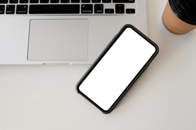 白いテーブルトップビューでスマートフォンとコンピューターを閉じます。白い画面のモックアップ