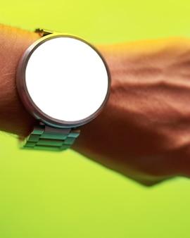 孤立した、空白の画面fと明るいライム緑の背景に手のひらにスマートな時計を閉じます