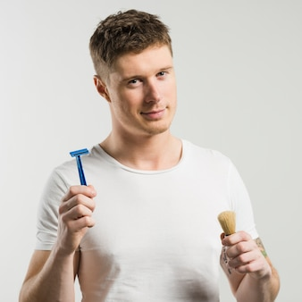 Close-up of smart young man holding razor and shaving brush in hands against white backdrop