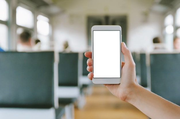 Close up of smartphone in the hands of woman against the background of train carriage