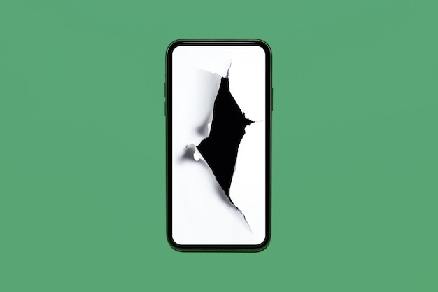 Close-up of smartphone with hole in white paper on screen, isolated on pastel green background.