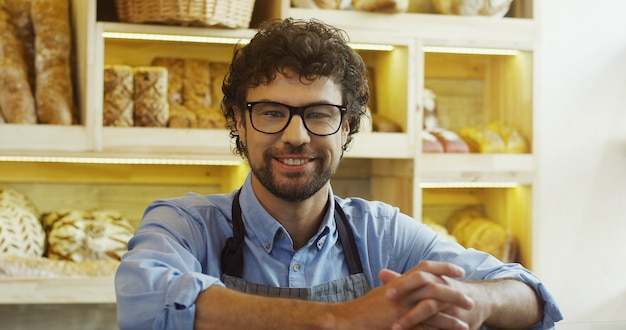 Close up of the smiled attractive male seller in glasses posing to the camera in the bakery shop at the counter. portrait. indoors