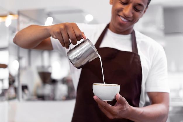Primo piano barista sorridente che prepara il caffè