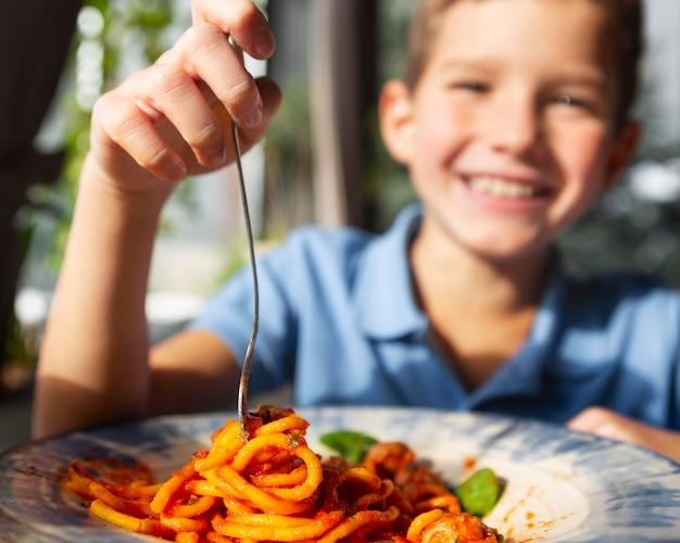 スパゲッティを食べる笑顔の少年を閉じる