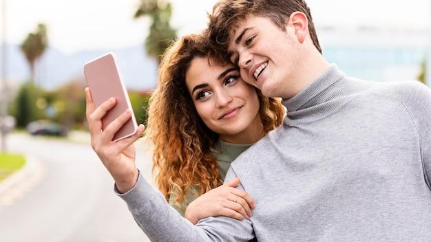 Coppie di smiley del primo piano che prendono selfie all'aperto