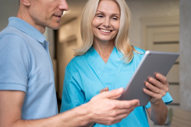 Close up smiley doctor holding tablet