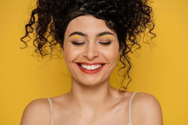 노란색 배경으로 근접 웃는 여성