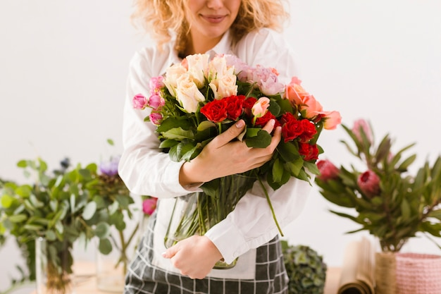 Close-up smiley florist holding jar with flowers