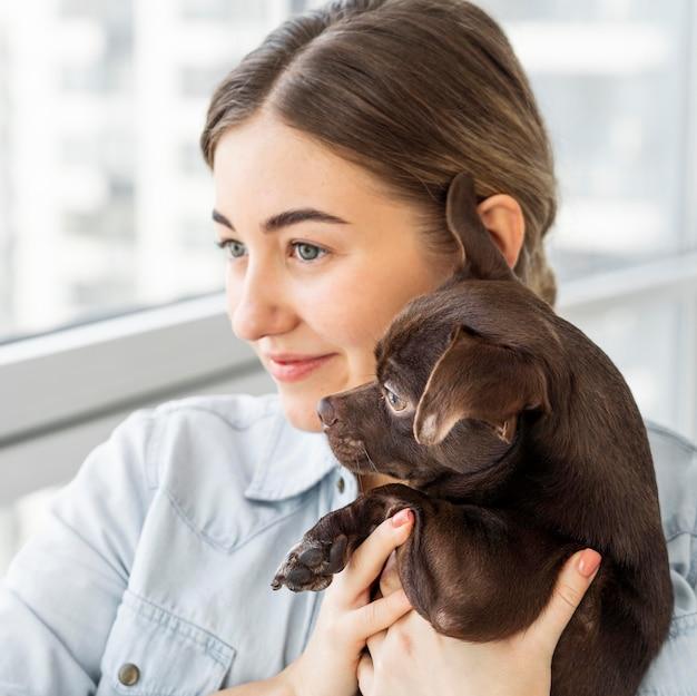 Крупным планом смайлик девушка держит собаку