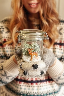 Close-up smiley girl holding jar with deer