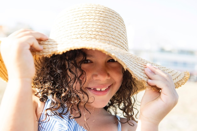 Close up smiley girl wearing hat on beach