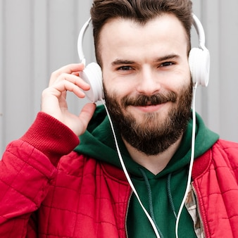 Close-up smiley guy with beard and headphones