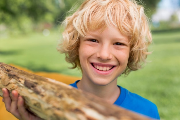Close up bambino sorridente che trasporta log