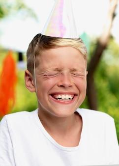 Primo piano ragazzo sorridente con cappello da festa