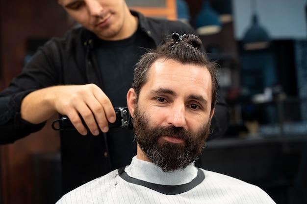 散髪をしている笑顔の男をクローズアップ
