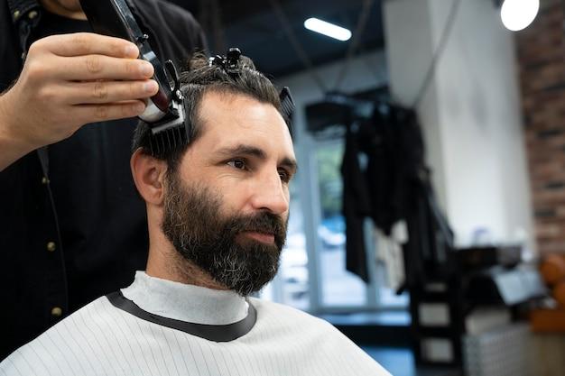 Close up smiley man getting a haircut
