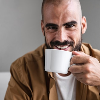 Close-up smiley man holding cup