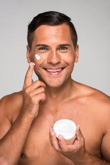 Крупным планом смайлик мужчина держит крем для лица