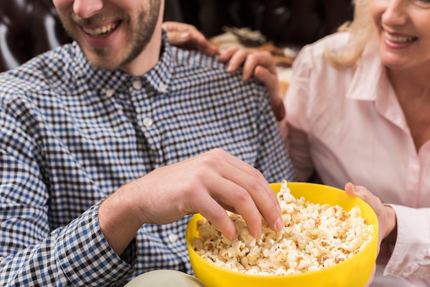 Close-up of smiley man holding popcorn bowl