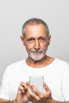 Uomo di smiley del primo piano che tiene smartphone