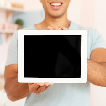 Close-up smiley man holding tablet