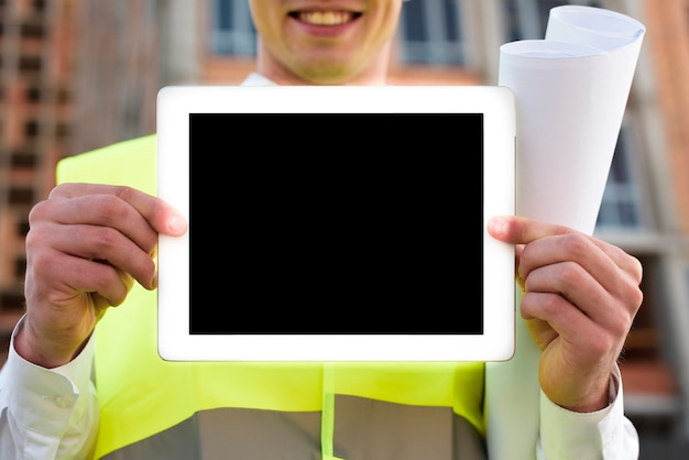Close-up smiley man holding up a tablet