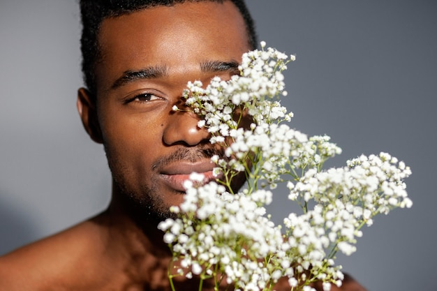 Uomo di smiley del primo piano che posa con i fiori