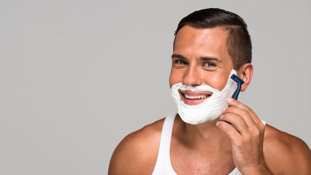 Close-up smiley man shaving