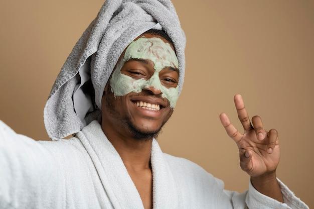 Primo piano uomo sorridente con maschera facciale