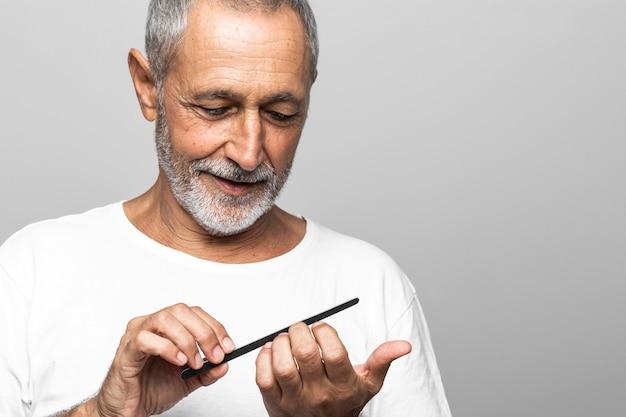 Close-up smiley senior man filing his nails