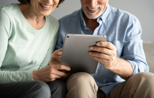 Close up smiley seniors with tablet