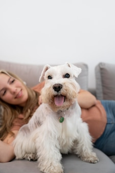 ソファの上の笑顔の女性と犬をクローズアップ