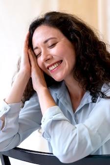 Close up donna sorridente sulla sedia