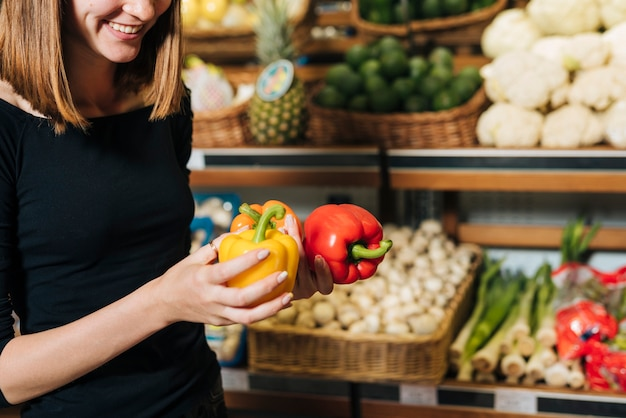 Close-up smiley woman holding bell peppers